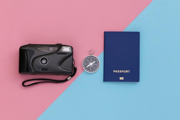 Viagem de minimalismo, aventura plana lay. câmera, passaporte e bússola em um fundo pastel rosa-azulado. vista do topo