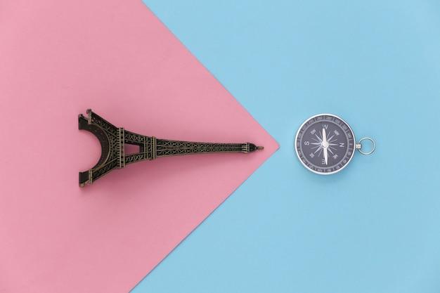 Viagem de minimalismo, aventura plana lay. estatueta de câmera e torre eiffel em um fundo azul-rosa pastel. vista do topo