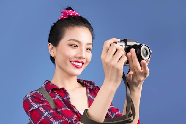 Viagem de mulher. jovem e linda mulher asiática tirando fotos em fundo azul