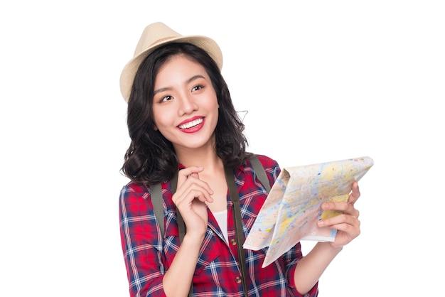 Viagem de mulher. viajante jovem linda mulher asiática observando o mapa em pé sobre o branco.