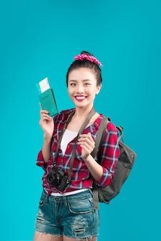 Viagem de mulher. viajante jovem linda mulher asiática segurando o passaporte e a passagem aérea em pé sobre o azul.