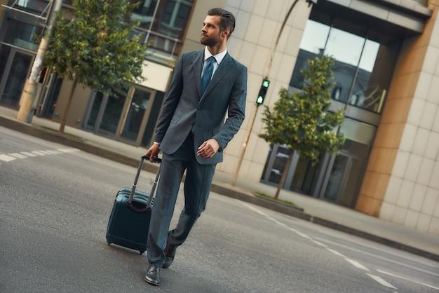 Viagem de negócios de comprimento total de jovem e bonito homem barbudo de terno puxando sua bagagem