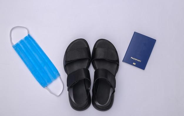 Viagem durante a pandemia covid-19. sandálias, máscara médica e passaporte em fundo branco. vista do topo
