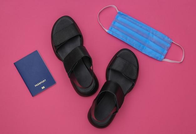 Viagem durante a pandemia covid-19. sandálias, máscara médica e passaporte em um fundo rosa. vista do topo