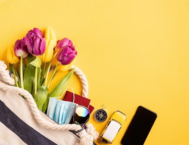 Viagem e aventura. equipamento de viagem plano com passaportes, smartphone, óculos de sol e bússola em fundo amarelo com espaço de cópia