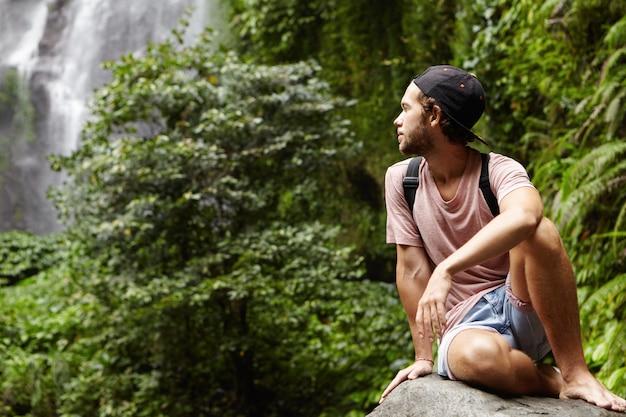 Viagem e aventura. jovem bonito caminhante descalço com uma mochila relaxando sozinho em uma pedra grande e olhando para trás