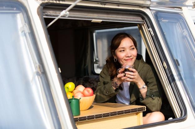 Viagem em família de carro de caravana em belas férias. jovem mulher asiática em caravana com uma xícara de café branca de manhã