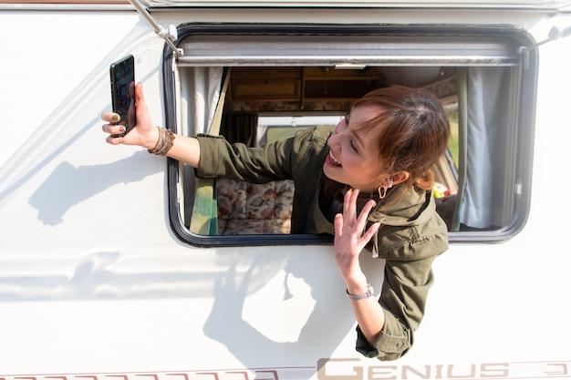 Viagem em família de carro de caravana em belas férias. selfie jovem asiática com smartphone em caravana com xícara de café branco pela manhã