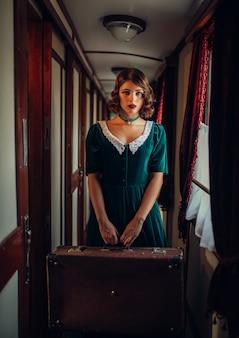Viagem ferroviária, mulher com mala em trem retrô, rico interior. vagão velho. viagem de trem