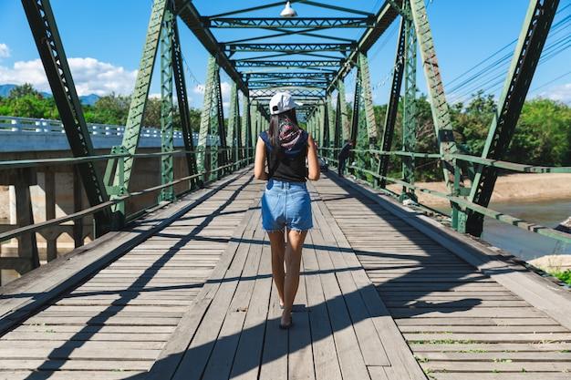Viagem individual relaxa conceito de férias, jovem viajante asiática passeando pela ponte pai memorial em pai, chiang mai, tailândia