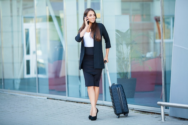 Viagem. jovem entra no aeroporto na janela com mala esperando o avião