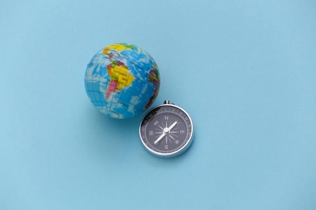 Viagem minimalista, aventura. bússola e globo em um fundo azul pastel. vista do topo.