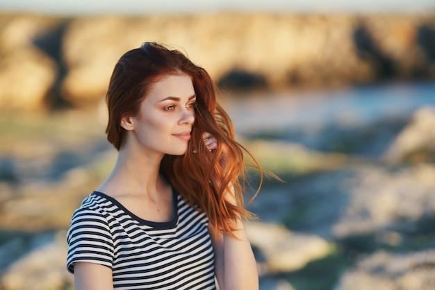 Viagem modelo listrado t-shirt montanhas paisagem rio cabelo vermelho. foto de alta qualidade
