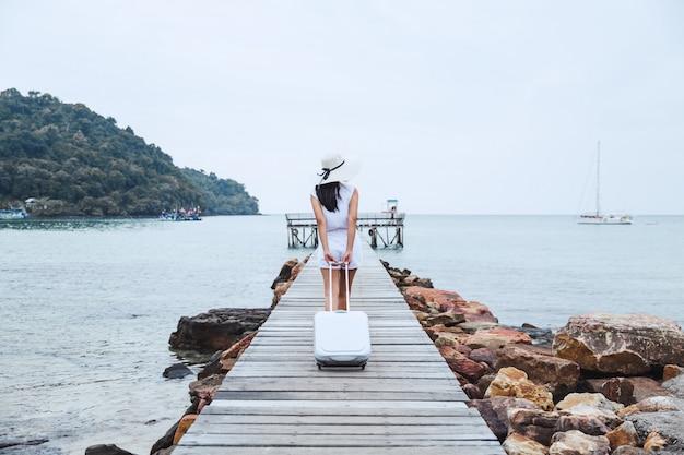 Viagem mulher com mala na praia