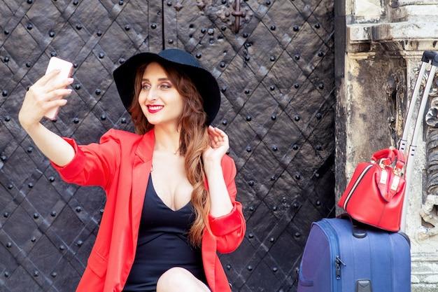 Viagem mulher de chapéu preto com mala faz selfie perto de porta preta velha.