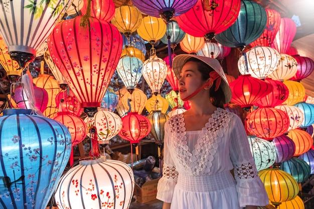 Viagem mulher escolhendo lanternas em hoi an, vietnam