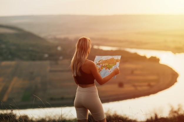 Viagem mulher lendo mapa ao pôr do sol incrível, apreciar a paisagem da natureza. ela segurando mapa turístico e planejamento de rota nas montanhas