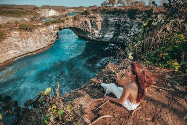 Viagem mulher olhando a vista de praia quebrada, ilha de nusa penida bali, indonésia