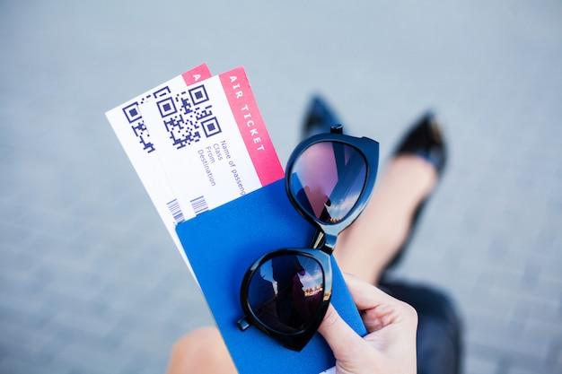 Viagem. mulher segurando duas passagens aéreas no exterior passaporte perto do aeroporto