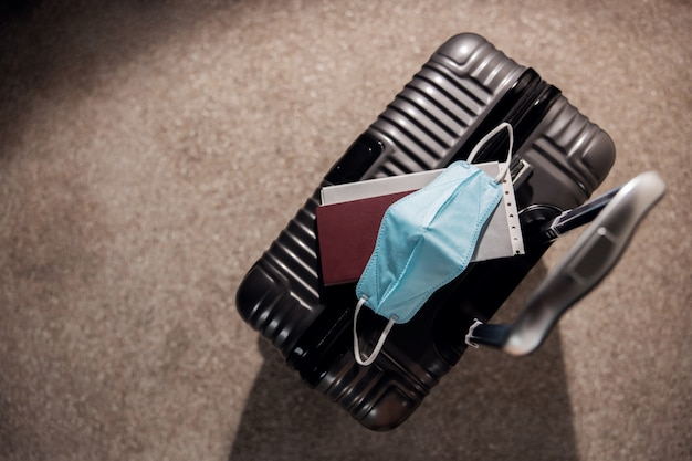 Viagem no conceito de situação do coronavirus. vista superior da bagagem, passaporte e máscara cirúrgica. caminho para proteção e segurança da covid-19