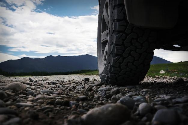 Viagem off-road na estrada da montanha. a roda do suv em primeiro plano, na estrada de pedra de cascalho.