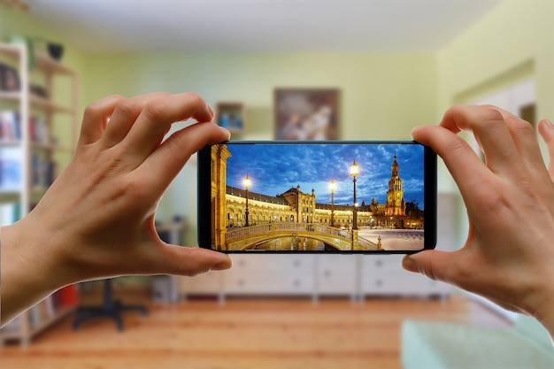 Viagem online para sevilha, espanha, de casa usando um telefone celular. plaza de espana na tela do smartphone