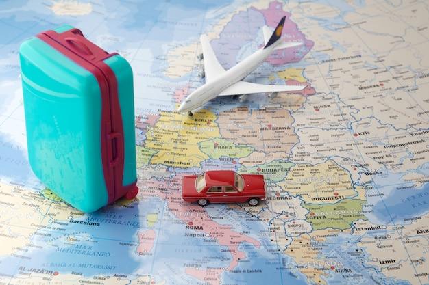 Viagem ou viajando pelo conceito de avião. avião de brinquedo em miniatura e malas no mapa.