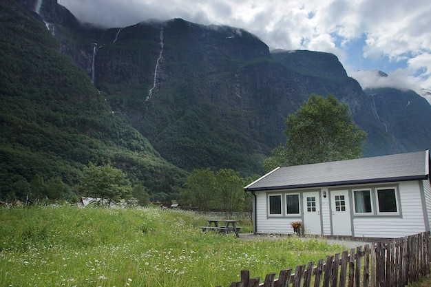 Viagem para a noruega, uma pequena casa fica em uma clareira perto de uma alta montanha.