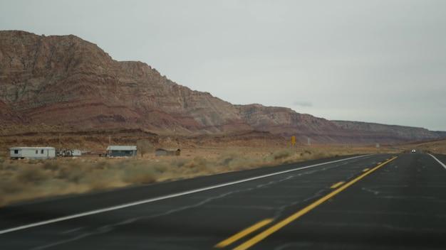Viagem para o grand canyon, arizona, eua, dirigindo automóvel de utah. rota 89. pegando carona viajando na américa, viagem local, atmosfera calma do oeste selvagem das terras indígenas. vista da estrada através do pára-brisa do carro.