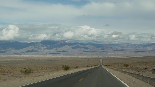Viagem para o vale da morte, dirigindo um automóvel na califórnia, eua. pegando carona viajando pela américa. rodovia, montanhas e deserto seco, deserto de clima árido. ponto de vista do passageiro do carro. viagem a nevada.