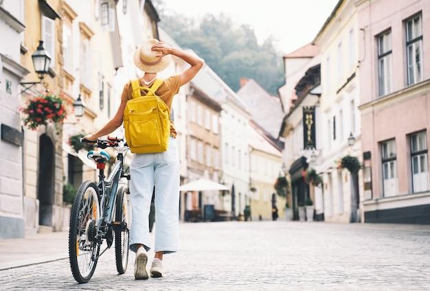 Viagem pela europa jovem com mochila e bicicleta urbana em uma rua antiga no centro de ljubljana