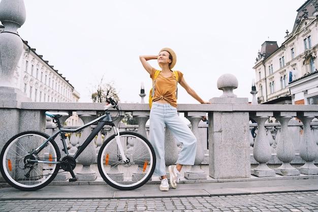 Viagem pela europa jovem garota com uma bicicleta urbana na triple bridge, no centro da cidade velha de ljubljana