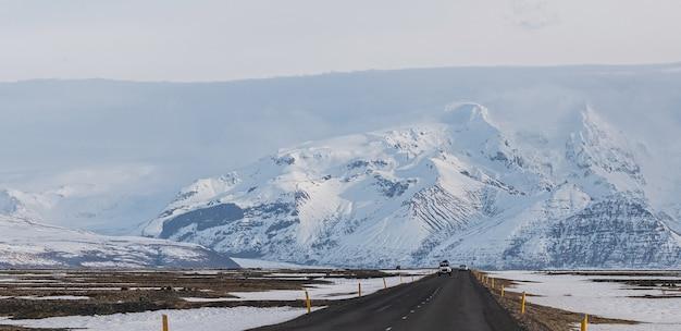 Viagem por estrada e conceito de férias. uma longa estrada que leva a montanhas cobertas de neve na islândia
