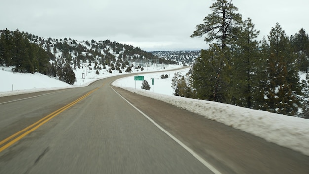 Viagem por estrada nos estados unidos de zion a bryce canyon dirigindo um automóvel em utah pedindo carona viajando na américa rota para dixie forest inverno jornada local atmosfera calma e neve vista das montanhas do carro