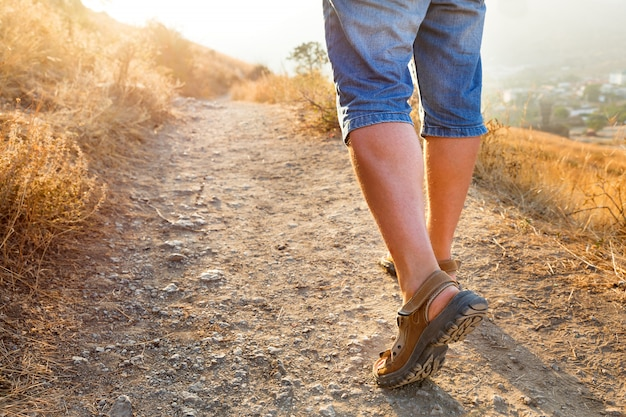 Viagem saudável ativa - homem em sandálias de esportes sobe na montanha.