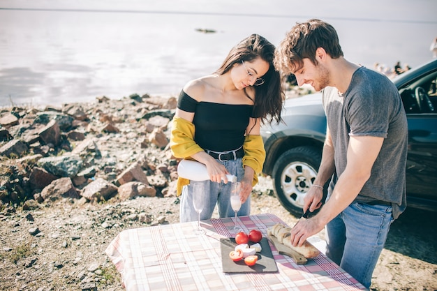 Viagem, turismo - homem e mulher bebem champanhe perto da água em uma mesa dobrável portátil. piquenique perto da água. casal vai em aventura. conceito de viagens de carro.