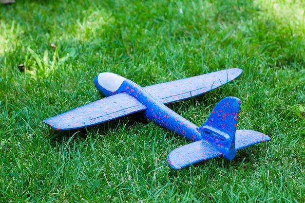 Viagem, viagem, conceito de férias. avião na grama verde. brinquedo infantil. fundo verde da natureza.