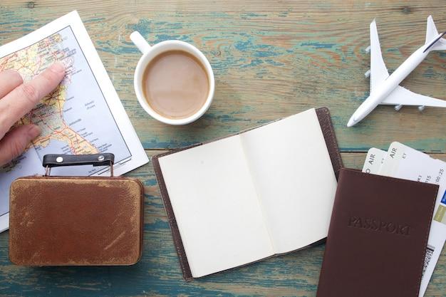 Viagem, viagem de férias, turismo - feche o caderno, a mala, o avião de brinquedo e o mapa turístico na mesa de madeira.
