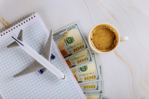 Viagens de férias, planejamento de notebook com avião, férias, notas de dólar, xícara de café com viagens de férias de avião