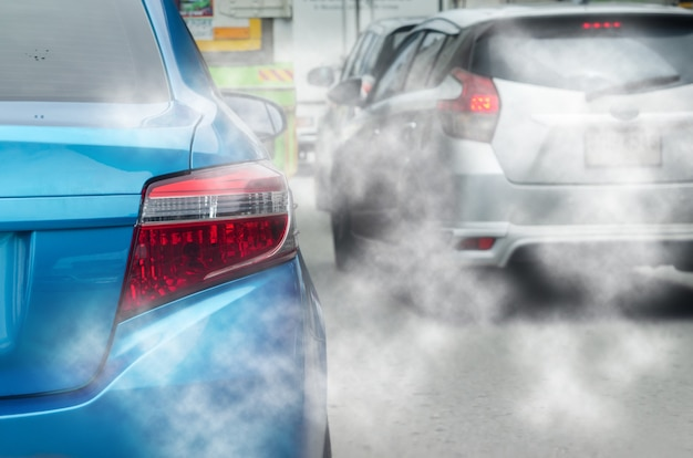 Viagens de transporte engarrafamentos em estradas com poluição do ar, fumaça de escapamento de automóveis. foco nas lanternas traseiras do carro.