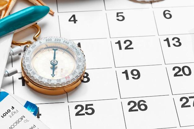 Viagens e férias, bússola no calendário planejador