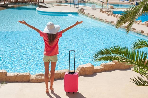 Viagens, férias de verão e conceito de férias. mulher bonita levanta as mãos perto da piscina do hotel.