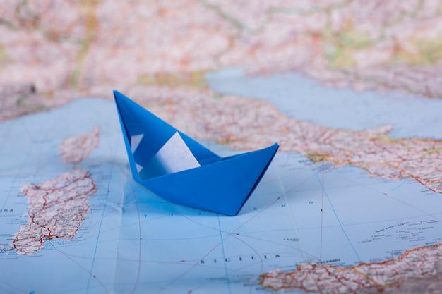 Viagens férias férias conceito origami turista artesanal papel papercraft navio no mapa perto da itália close-up