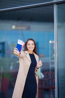 Viagens, mulher segurando duas passagens aéreas no exterior passaporte perto do aeroporto
