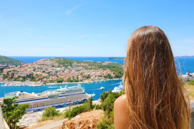 Viagens no mediterrâneo. mulher jovem, apreciando a vista da costa da croácia da cidade de dubrovnik. férias de verão na europa.
