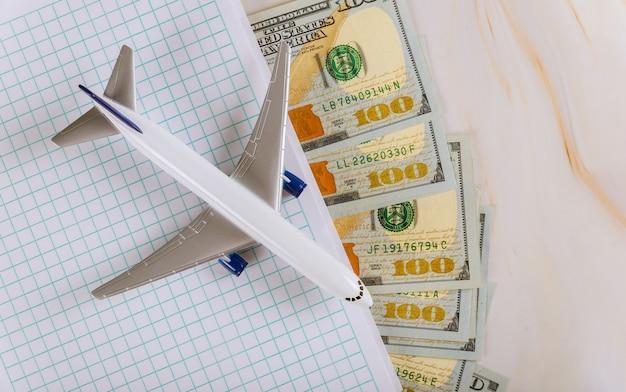 Viagens, planejamento de notebook com avião, férias, notas de dólar dos eua com férias de avião