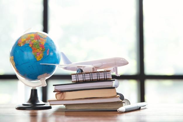 Viagens, viagem de férias, close-up de avião de brinquedo, caneta e bloco de notas e globo na mesa de madeira