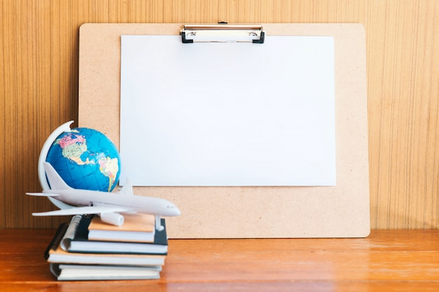 Viagens, viagem de férias, placa de papel branco, avião de brinquedo e bloco de notas e globo na mesa de madeira