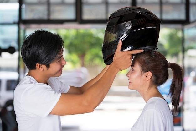 Viajando casal em pé e usando um capacete de moto