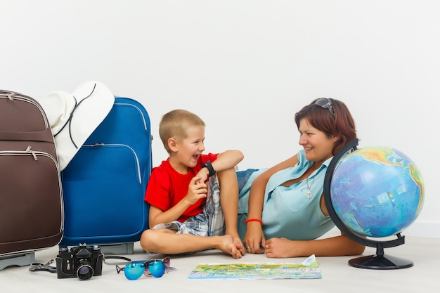 Viajando com crianças. mãe feliz com seu filho roupas de embalagem para as suas férias